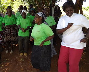 Mercy Karunditu, GBM Senior Project Officer, dances with Kimara G3 Self-help Group in Kangema.
