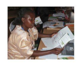 Veronica Gitahi, a GBM field facilitator, studies her training materials.
